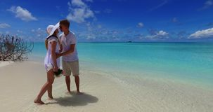 V07478 Maldives white sandy beach 2 people a young couple man woman standing together in love on sunny tropical paradise Royalty Free Stock Photo