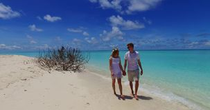 V07516 Maldives white sandy beach 2 people a young couple man woman walking together in love on sunny tropical paradise. Maldives white sandy beach 2 people a stock video footage