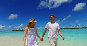 V07520 Maldives white sandy beach 2 people a young couple man woman walking together in love on sunny tropical paradise. Maldives white sandy beach 2 people a stock video