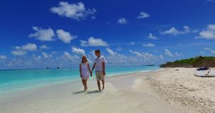 V07526 Maldives white sandy beach 2 people a young couple man woman walking together in love on sunny tropical paradise. Maldives white sandy beach 2 people a stock footage