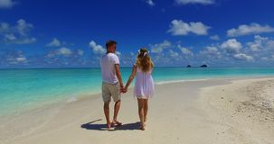 V07519 Maldives white sandy beach 2 people a young couple man woman walking together in love on sunny tropical paradise Royalty Free Stock Image