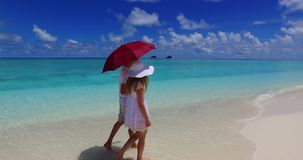 V07508 Maldives white sandy beach 2 people a young couple man woman walking together in love on sunny tropical paradise Stock Photos