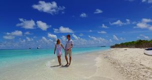 V07526 Maldives white sandy beach 2 people a young couple man woman walking together in love on sunny tropical paradise Royalty Free Stock Photo