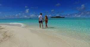 V07485 Maldives white sandy beach 2 people a young couple man woman walking together in love on sunny tropical paradise. Maldives white sandy beach 2 people a Royalty Free Stock Images