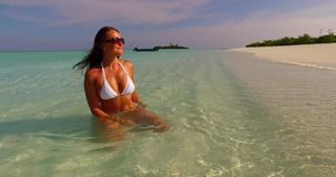 V07876 Maldives white sandy beach 1 person young beautiful lady sunbathing alone on sandbar on sunny tropical paradise. Maldives white sandy beach 1 person young stock video footage
