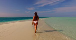 V07898 Maldives white sandy beach 1 person young beautiful lady sunbathing alone on sandbar on sunny tropical paradise