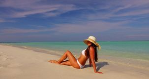 V07873 Maldives white sandy beach 1 person young beautiful lady sunbathing alone on sandbar on sunny tropical paradise. Maldives white sandy beach 1 person young stock video footage
