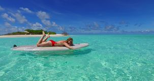 V07343 Maldives white sandy beach  woman paddleboard rowing on sunny tropical paradise island. Maldives white sandy beach young woman paddleboard rowing on sunny stock footage