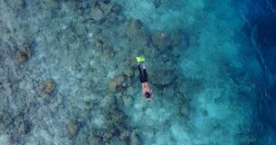 V11880 many people young boys girls snorkeling over coral reef with drone aerial flying view in crystal clear aqua blue. Many people young boys girls snorkeling stock video footage