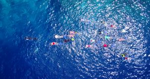 V11830 many people young boys girls snorkeling over coral reef with drone aerial flying view in crystal clear aqua blue. Many people young boys girls snorkeling royalty free stock photography