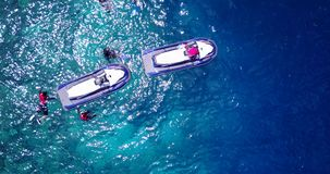 V11870 many people young boys girls snorkeling over coral reef with drone aerial flying view in crystal clear aqua blue Stock Photo