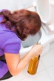 Vômito da mulher da bebida em uma bacia de toalete Imagens de Stock