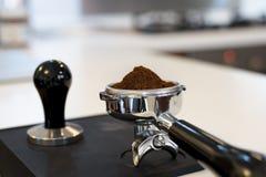 V.N.-Tamped koffiedik in een portafilter stock afbeeldingen