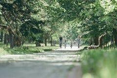 V?nliga familjer p? en cykelritt i staden parkerar royaltyfria bilder