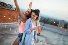 V?nner som har partiet ?verst av taket Gyckel, sommar, stadslivsstil och kamratskapbegrepp royaltyfria foton