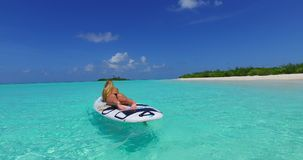 V11916 one 1 beautiful young girl in bikini sunbathing on surfboard paddleboard and relaxing by the aqua blue sea water Stock Photography
