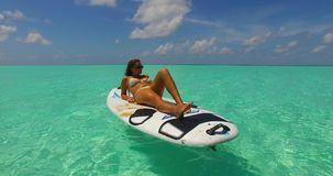 V11955 one 1 beautiful young girl in bikini sunbathing on surfboard paddleboard and relaxing by the aqua blue sea water Royalty Free Stock Photo