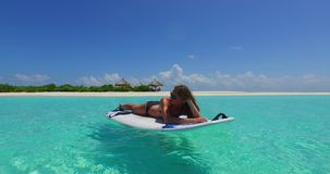 V11950 one 1 beautiful young girl in bikini sunbathing on surfboard paddleboard and relaxing by the aqua blue sea water Stock Images