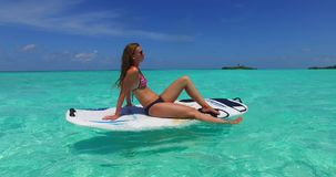 V11971 one 1 beautiful young girl in bikini sunbathing on surfboard paddleboard and relaxing by the aqua blue sea water Stock Photography