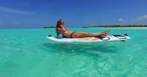 V11964 one 1 beautiful young girl in bikini sunbathing on surfboard paddleboard and relaxing by the aqua blue sea water Stock Image
