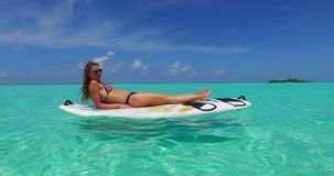 V11962 one 1 beautiful young girl in bikini sunbathing on surfboard paddleboard and relaxing by the aqua blue sea water Stock Images