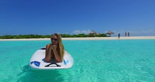 V11918 one 1 beautiful young girl in bikini sunbathing on surfboard paddleboard and relaxing by the aqua blue sea water Royalty Free Stock Photo