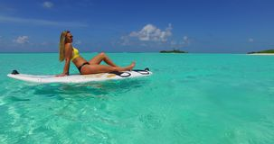 V11925 one 1 beautiful young girl in bikini sunbathing on surfboard paddleboard and relaxing by the aqua blue sea water Royalty Free Stock Images