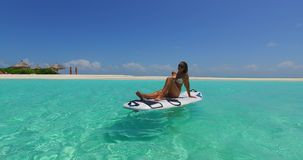 V11912 one 1 beautiful young girl in bikini sunbathing on surfboard paddleboard and relaxing by the aqua blue sea water Royalty Free Stock Photo