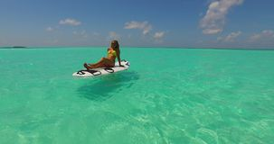 V11929 one 1 beautiful young girl in bikini sunbathing on surfboard paddleboard and relaxing by the aqua blue sea water Stock Photo