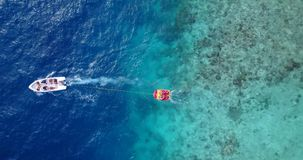 V09406 People enjoying boats and watersports with view from aerial flying drone in clear aqua blue sea water and blue. People enjoying boats and watersports with Royalty Free Stock Photos