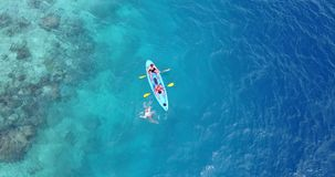 V09385 People enjoying boats and watersports with view from aerial flying drone in clear aqua blue sea water and blue. People enjoying boats and watersports with stock photo