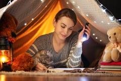 V??r bedtijd Een meisje met een Schotse en Britse kat die een boek in een tent lezen Een concept rust, sprookjes, nacht, slaap en royalty-vrije stock afbeeldingen