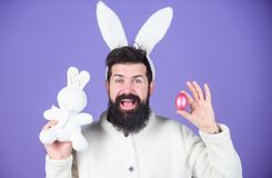 V?r, nytt liv och fertilitet Lycklig man med kanin?ron som rymmer det kaninleksaken och ?gget Sk?ggig man i kanindr?kt med arkivfoto