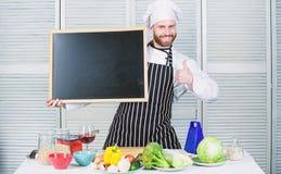 V?r skola ?r den b?sta mannen som visar upp tummar med det tomma br?det Utbildning av matlagning- och matf?rberedelsen h?gsta koc arkivfoton
