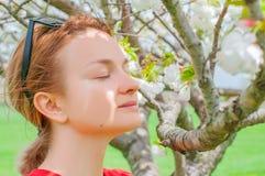V?rallergi H?rlig kvinna som tycker om det blommande tr?det f?r natur royaltyfria foton