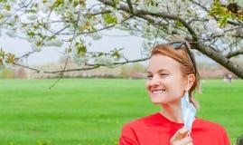 V?rallergi H?rlig kvinna som tycker om det blommande tr?det f?r natur arkivfoto