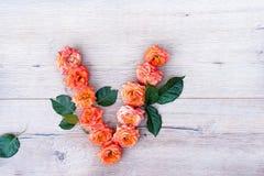 V, roses fleurissent l'alphabet d'isolement sur le fond en bois gris, configuration d'appartement Image stock