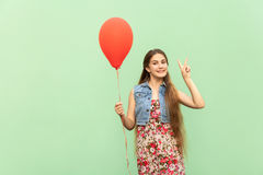 V sign! The beautiful blonde teenager with red ballons on a green background. Royalty Free Stock Photos