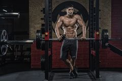 A young man with a strong body, a man with an ideal figure, hold Royalty Free Stock Image