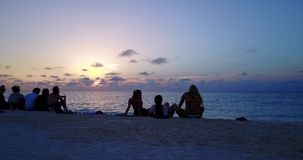 V12784 sunset sunrise group of young beautiful girls on beach with drone aerial flying view of evening morning clear sea Royalty Free Stock Image