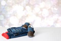 V?tements color?s de jeans d'enfants Thermojeans ray?s rouges ? la mode et une paire ? la mode d'espadrilles bleues sur la table  photographie stock libre de droits