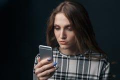 V?tima adolescente triste ser do cyber que tiraniza o assento em linha em um sof? na sala de visitas em foto de stock