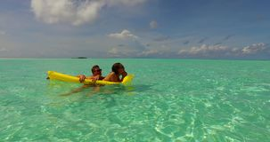 V13899 two 2 people inflatable sunbed romantic young people couple with drone aerial flying view on a tropical island of. Two 2 people inflatable sunbed romantic stock footage
