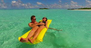 V13903 two 2 people inflatable sunbed romantic young people couple with drone aerial flying view on a tropical island of. Two 2 people inflatable sunbed romantic stock video