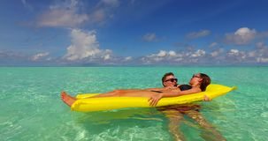 V13905 two 2 people inflatable sunbed romantic young people couple with drone aerial flying view on a tropical island of. Two 2 people inflatable sunbed romantic stock footage