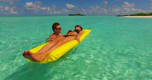 V13902 two 2 people inflatable sunbed romantic young people couple with drone aerial flying view on a tropical island of. Two 2 people inflatable sunbed romantic stock video footage