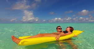 V13905 two 2 people inflatable sunbed romantic young people couple with drone aerial flying view on a tropical island of Stock Photos