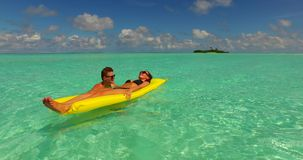 V13899 two 2 people inflatable sunbed romantic young people couple with drone aerial flying view on a tropical island of Royalty Free Stock Photo