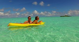 V13892 two 2 people inflatable sunbed romantic young people couple with drone aerial flying view on a tropical island of Royalty Free Stock Images