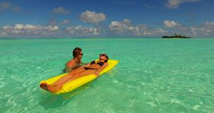 V13888 two 2 people inflatable sunbed romantic young people couple with drone aerial flying view on a tropical island of Stock Images